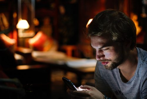This picture show a young man using his smartphone.